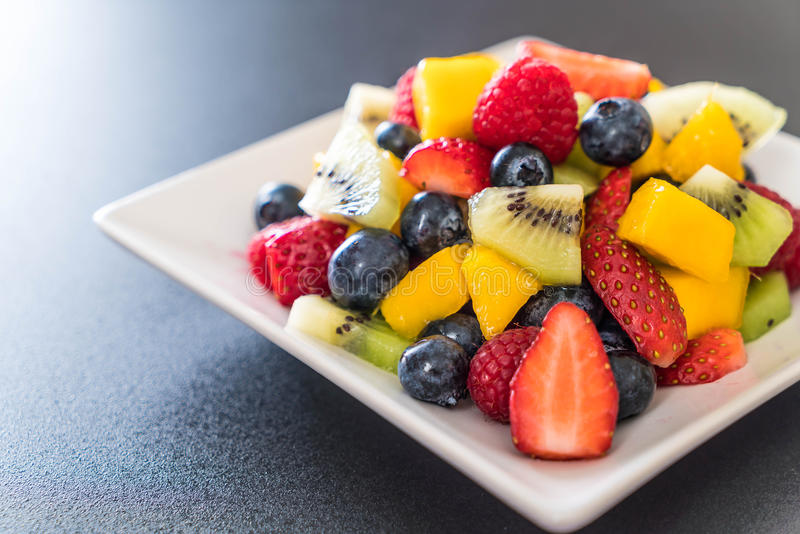 Mixed fresh fruits (strawberry, raspberry, blueberry, kiwi, mango). On white plate royalty free stock photography