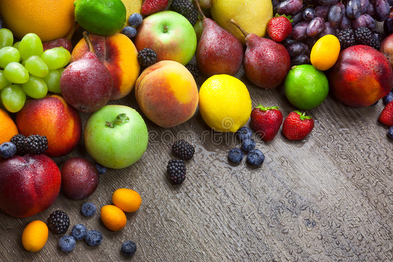 Mixed fresh Fruits on the wooden background with water drops royalty free stock photo