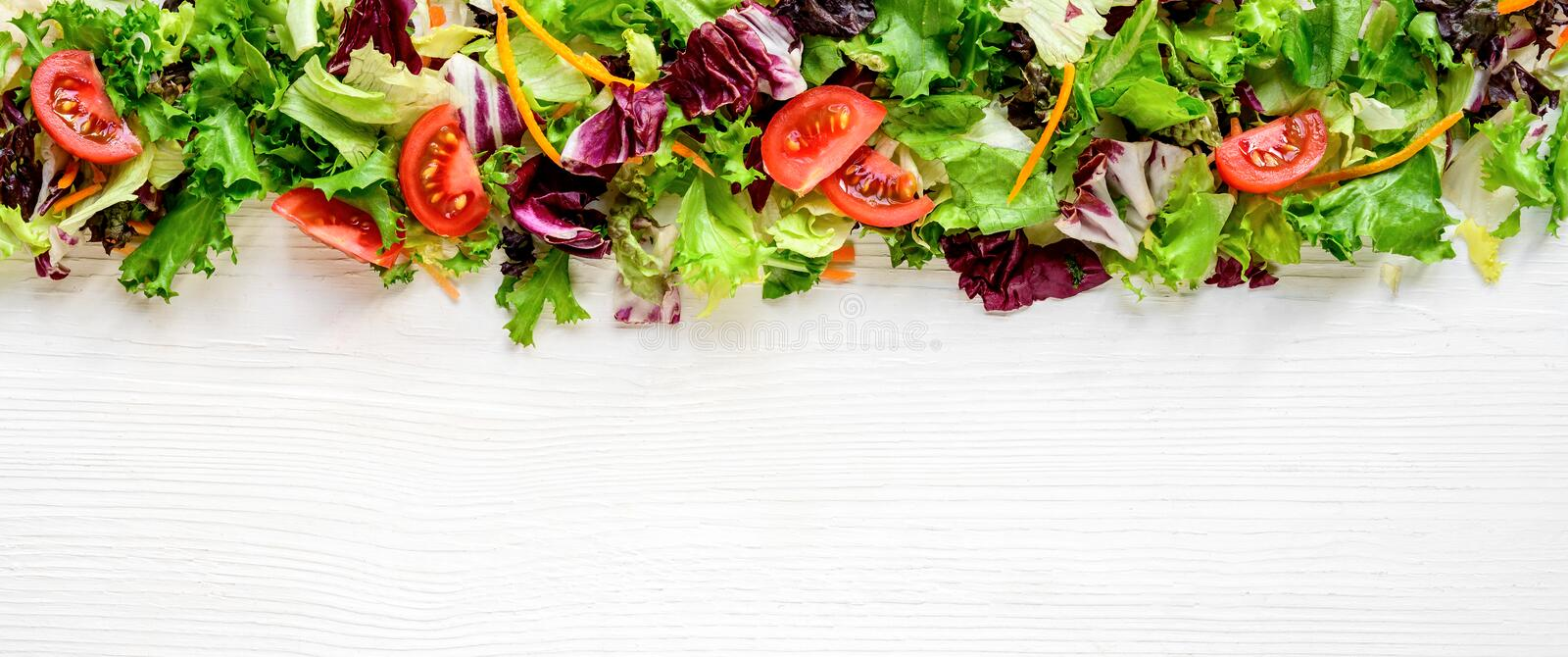 Mixed fresh salad leaves and vegetables on white wooden table. Background, border, frame, website header royalty free stock photo