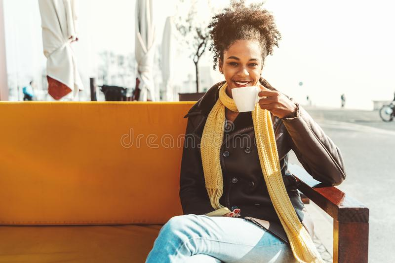 Mixed girl drinking coffee outdoors royalty free stock photo