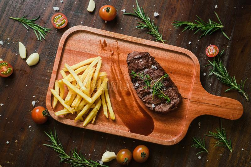 Mixed Grilled kebab grilled meat steak lies with french frieson a Rustic old elegant wooden cutlery cutting chopping board chili, royalty free stock photo