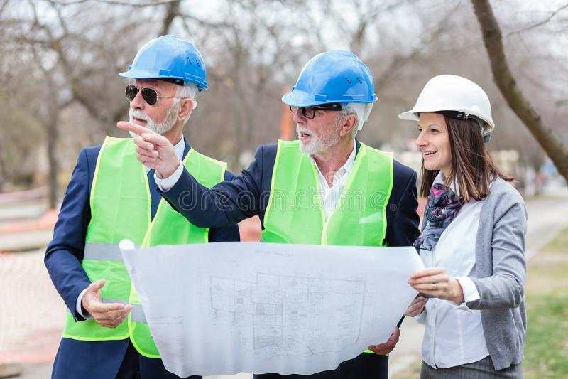 Mixed group of architects and business partners discussing project details during inspection of a construction site royalty free stock photos