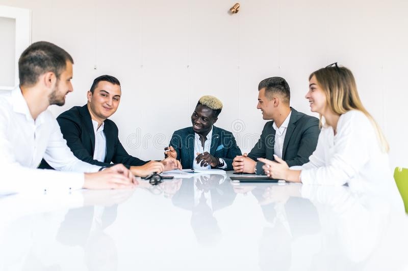 Mixed group in business meeting. Business team talk around table in modern office stock images