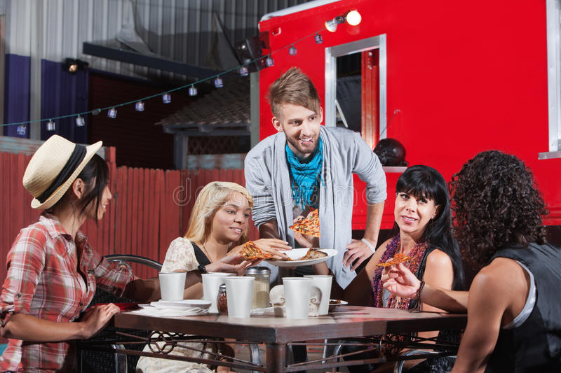 Mixed Group Eating at Restaurant. Mixed group of friends talking and eating pizza royalty free stock images