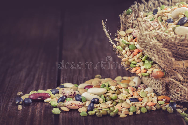 Mixed legumes and cereals. Mixed dried legumes and cereals in small burlap bag on dark wooden background. Copy space stock image