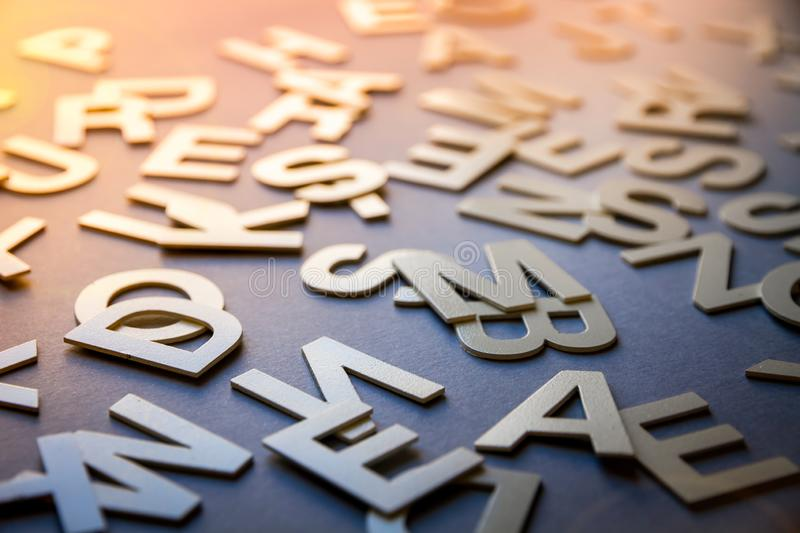 Mixed letters pile closeup photo. Mixed solid letters pile closeup photo. Education background concept stock photos