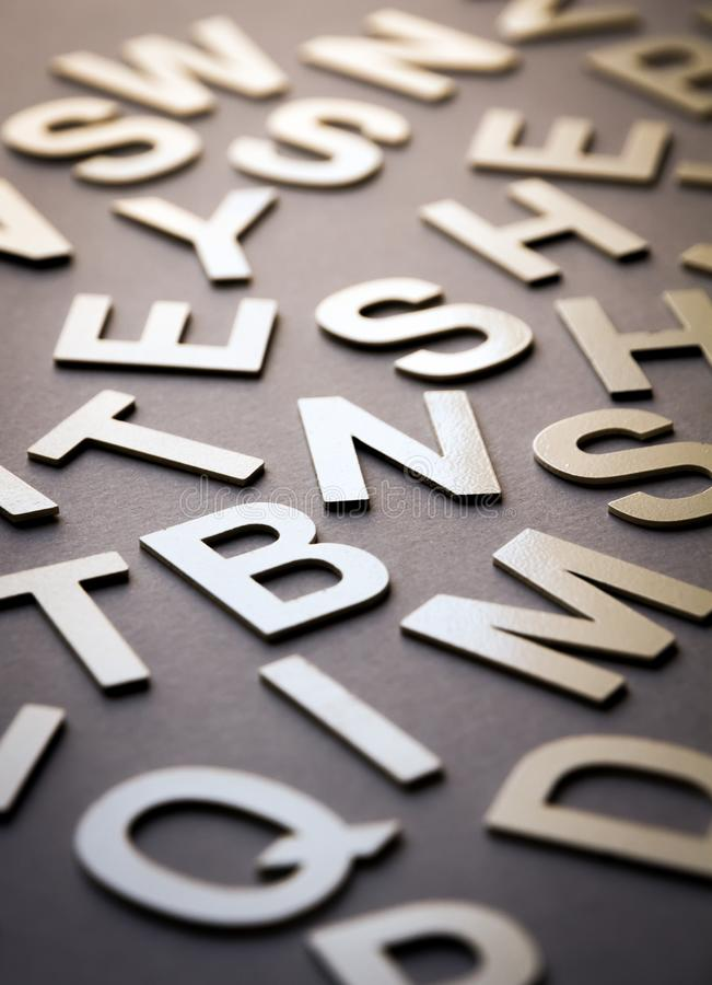 Mixed letters pile closeup photo. Mixed solid letters pile closeup photo. Education background concept stock images