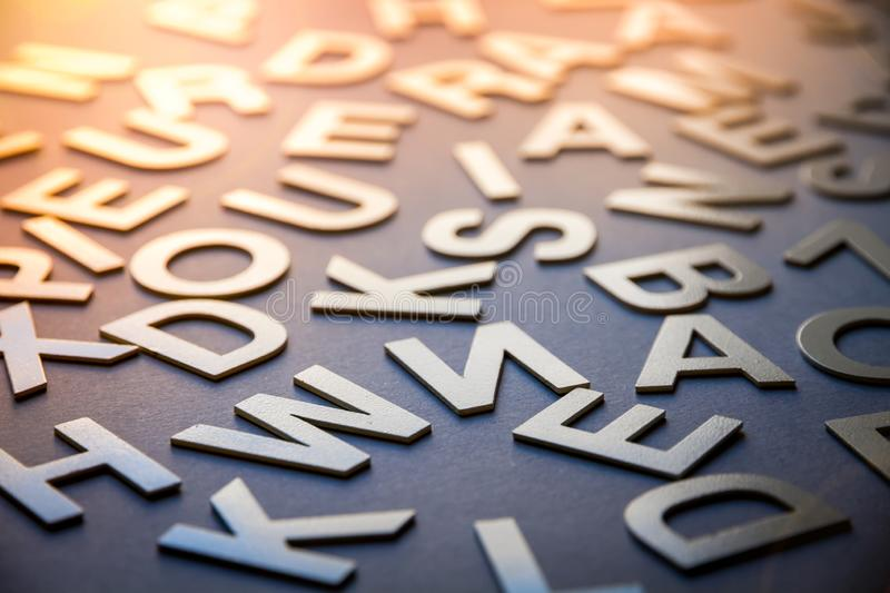 Mixed letters pile closeup photo. Mixed solid letters pile closeup photo. Education background concept royalty free stock image