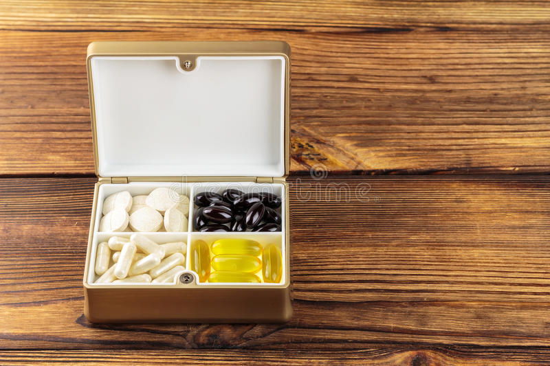 Mixed natural food supplement pills in container, omega 3, vitamin c, carotene capsules on wooden background royalty free stock photography