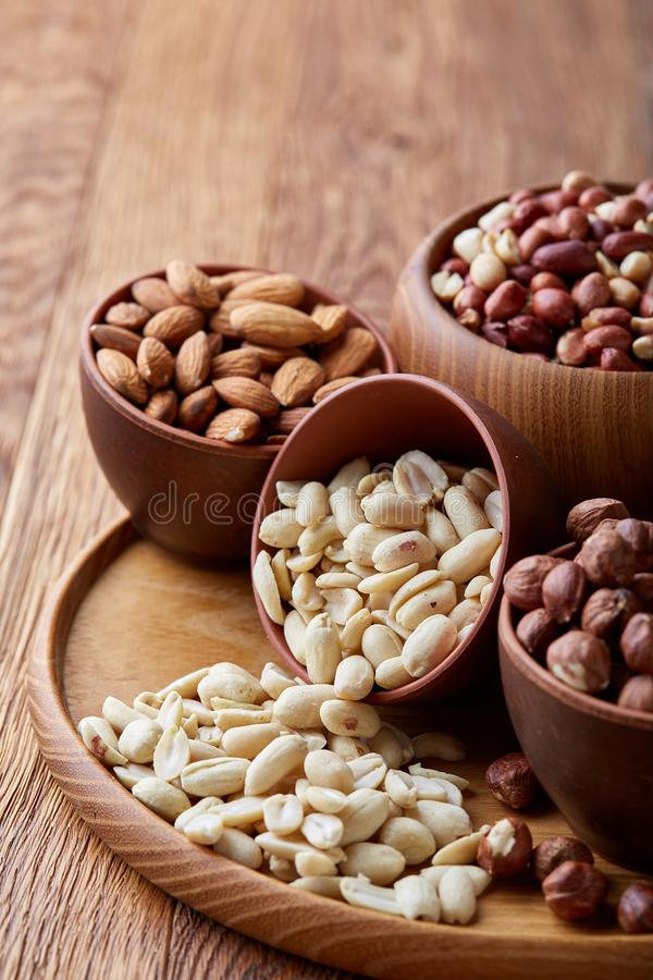 Mixed nuts in brown bowls on wooden tray over rustic background, close-up, top view, selective focus. stock photos