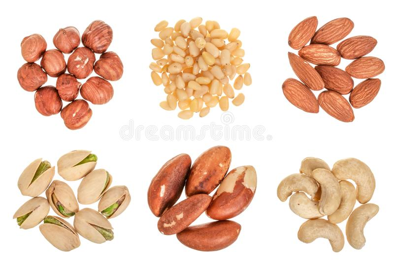 Mixed of nuts heap isolated on white background. Almonds, cashews, hazelnuts, pine and brazil nuts. Top view. Flat lay stock photo