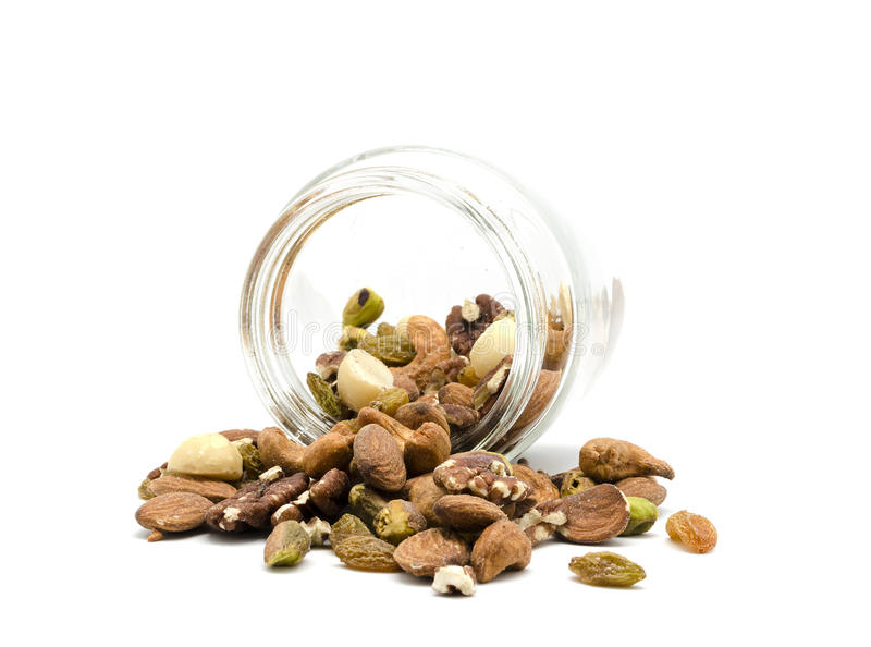 Mixed nuts. Spilling out from glass jar, isolated on white background stock image