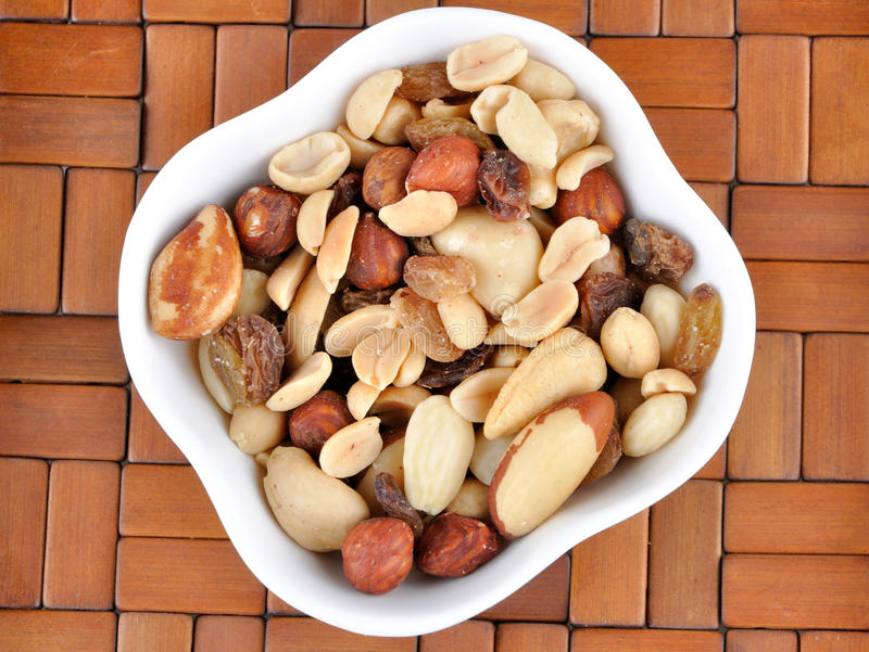 Mixed nuts in a white bowl stock photo
