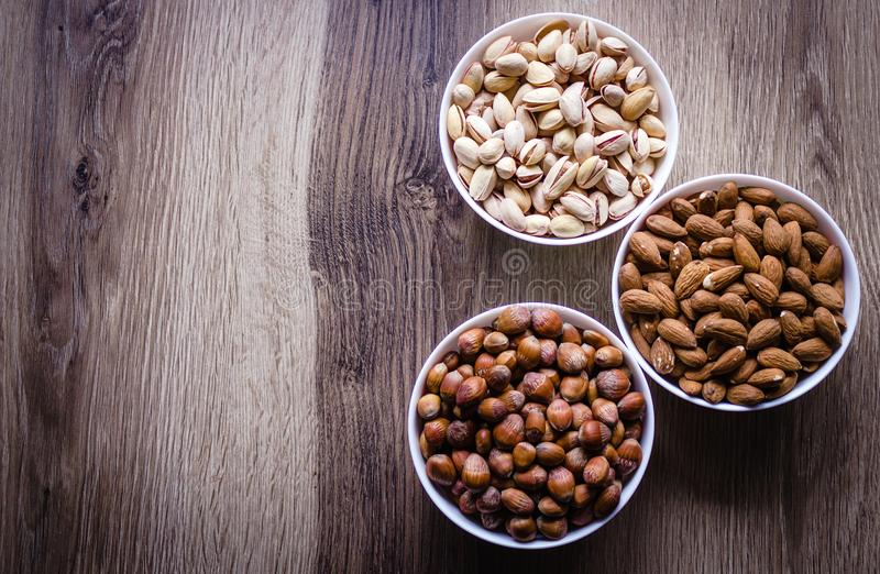 Mixed nuts in a white ceramic bowl on a wooden background. stock photos