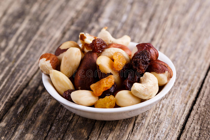 Mixed nuts on a white plate. Mixed nuts on a plate on wooden background stock image