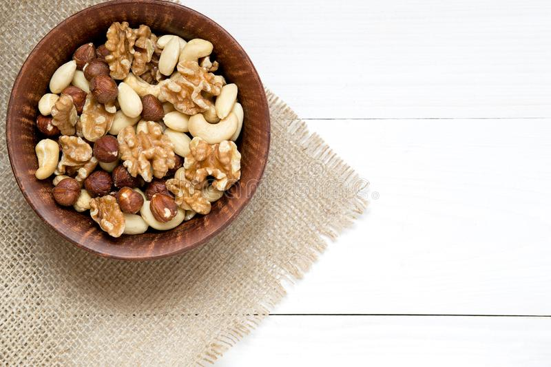 Mixed nuts in wooden bowl on the white wooden table. Background, copy space, top view, close up stock images