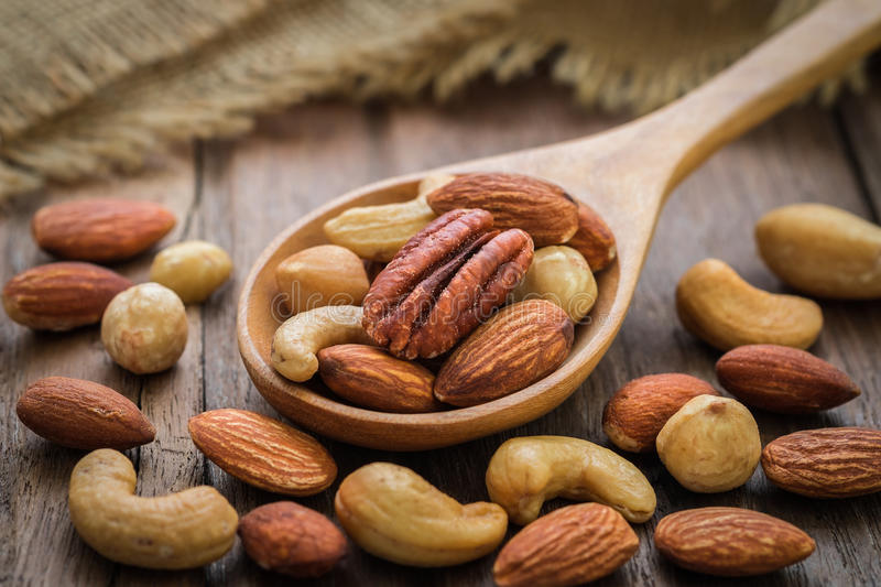 Mixed nuts on wooden spoon stock photo