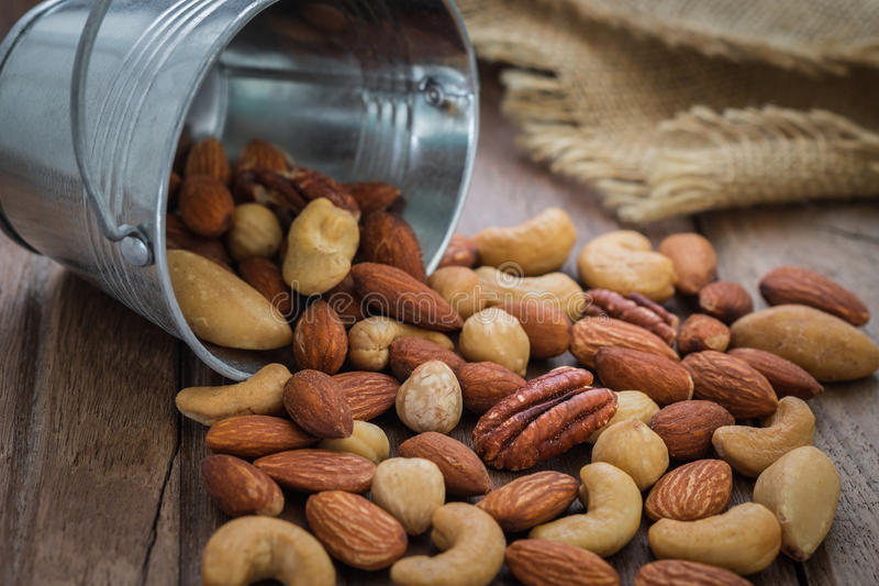 Mixed nuts on wooden table stock image