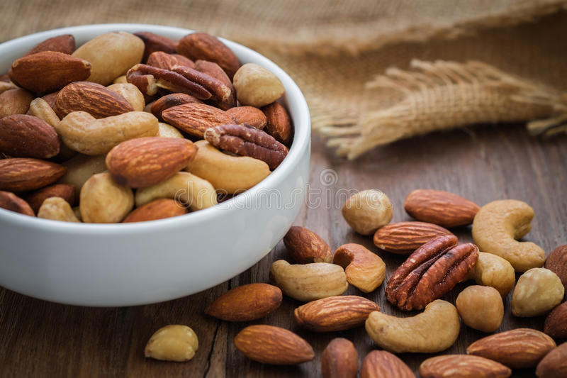 Mixed nuts on wooden table and bowl royalty free stock photo