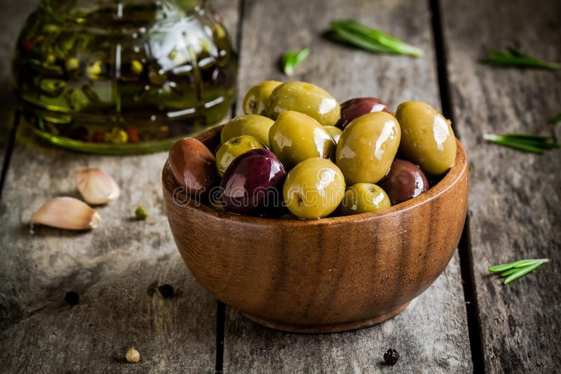 Mixed olives in a bowl with rosemary, olive oil and garlic on a rustic table stock photos