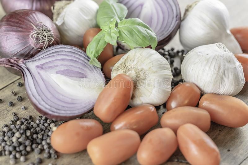 Mixed organic vegetables placed on rustic wooden table. Italian cooking ingredients.Mixed organic vegetables placed on rustic wooden background.Red onion, garlic stock image