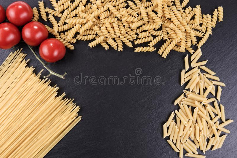 Mixed pasta varieties on black slate plate. Mixed raw pasta varieties on black slate plate stock photography