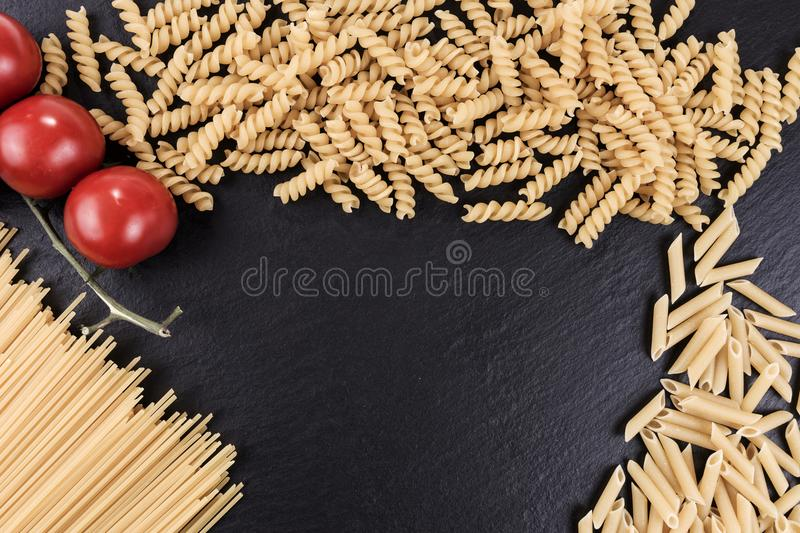 Mixed pasta varieties on black slate plate. Mixed raw pasta varieties on black slate plate royalty free stock photography