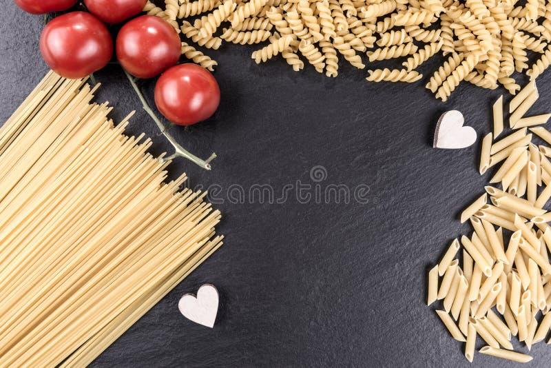 Mixed pasta varieties on black slate plate. Mixed raw pasta varieties on black slate plate stock photo