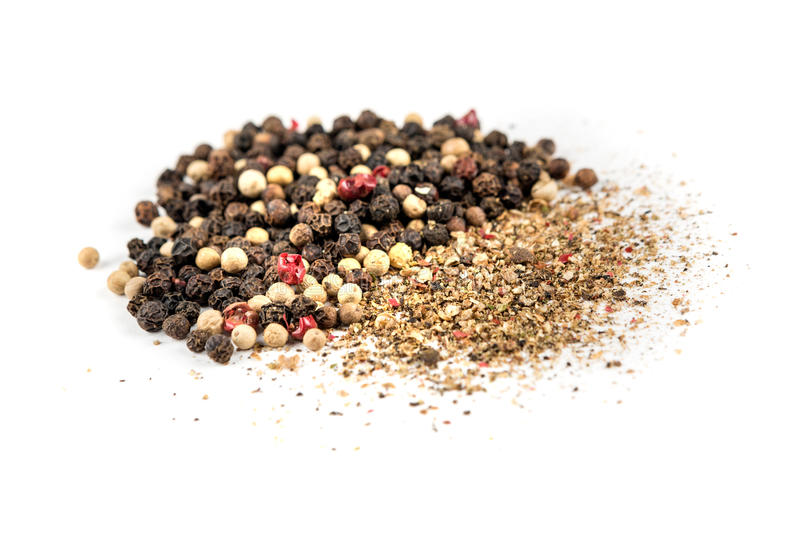Mixed peppercorns and ground pepper. Isolated on white background royalty free stock photo