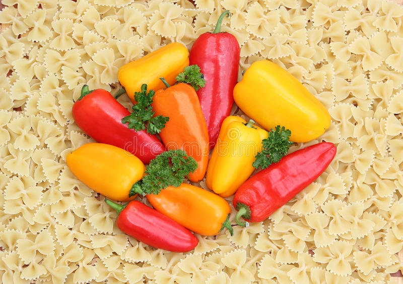 Mixed peppers on noodles background. Mixed fresh colorful peppers against farfalle noodles background royalty free stock images