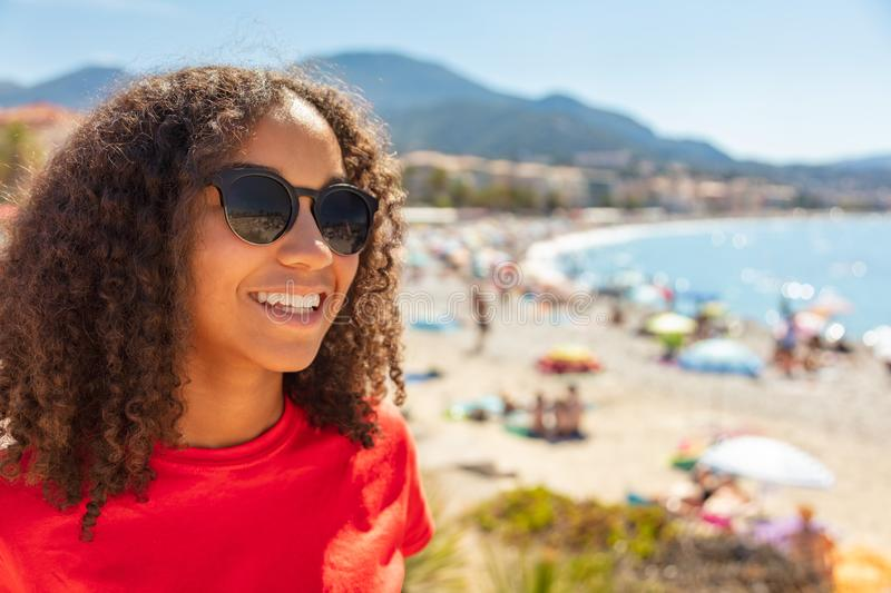 Mixed Race African American Girl Teen Sunglasses on Beach. Beautiful mixed race biracial African American female girl teenager young woman on vacation with royalty free stock images