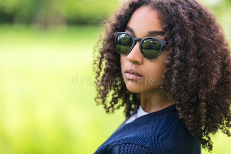 Mixed Race African American Girl Teen Sunglasses. A beautiful sad moody mixed race African American female girl child teenager young woman in sunshine wearing royalty free stock image