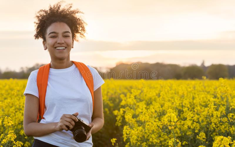 Mixed Race African American Girl Teenager With Camera in Yellow Flowers. Beautiful and happy mixed race African American girl teenager, female young woman stock image