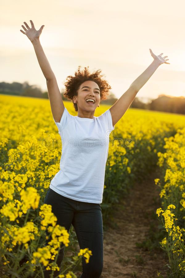 Mixed Race African American Girl Teenager Celebrating In Yellow Flowers. Outdoor portrait, in golden evening sunshine, of beautiful happy mixed race African stock photos