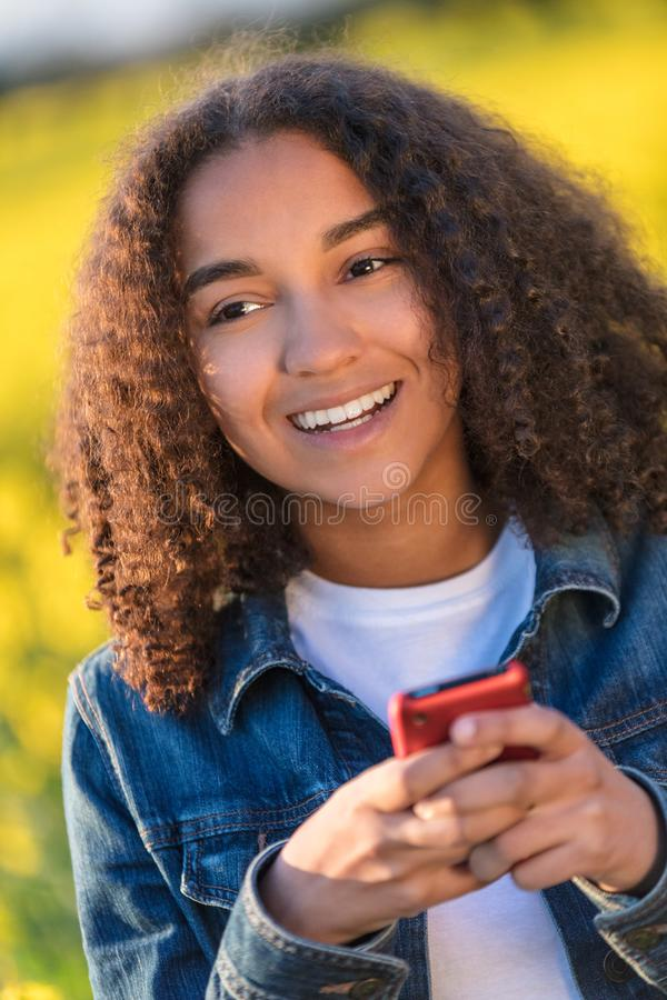 Mixed Race African American Girl Teenager on Cell Phone. Outdoor portrait of beautiful happy mixed race African American girl teenager female young woman smiling royalty free stock photo