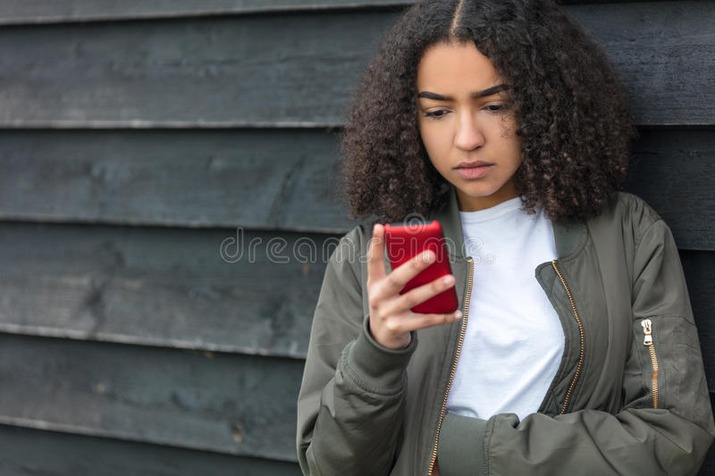 Mixed Race African American Girl Teenager on Cell Phone. Outdoor portrait of beautiful sad depressed mixed race African American girl teenager female young woman stock images