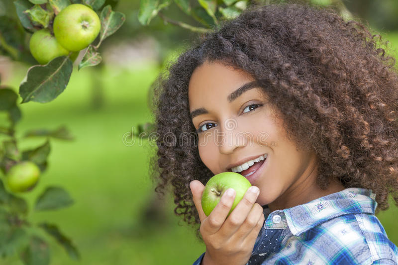 Mixed Race African American Girl Teenager Eating Apple stock images