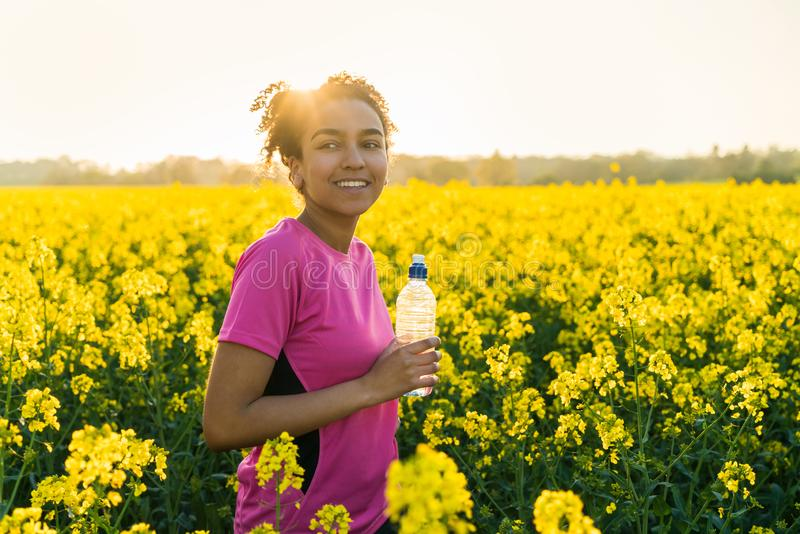 Mixed Race African American Girl Teenager Runner Drinking Water at Sunset. Outdoor portrait of beautiful, happy, mixed race biracial, African American girl royalty free stock photos
