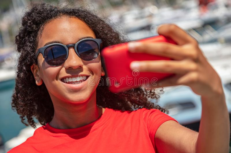 Mixed Race African American Girl Teenager Taking Selfie. Beautiful and happy mixed race African American young woman girl teenager female, wearing sunglasses and stock photo