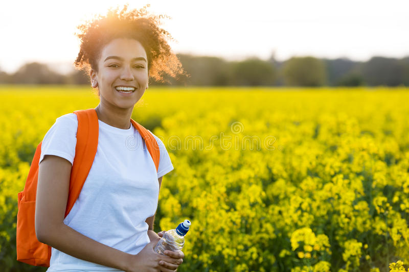 Mixed Race African American Girl Teenager In Yellow Flowers at S. Outdoor portrait of beautiful happy mixed race African American girl teenager female young stock photography