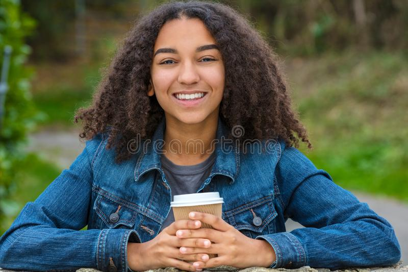 Mixed Race African American Teenager Woman Drinking Coffee. Beautiful happy biracial mixed race African American girl teenager female young woman smiling with stock photography