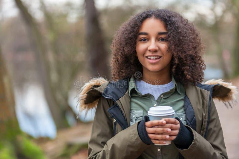 Mixed Race African American Teenager Woman Drinking Coffee. Beautiful happy mixed race biracial African American girl teenager female young woman smiling stock photo