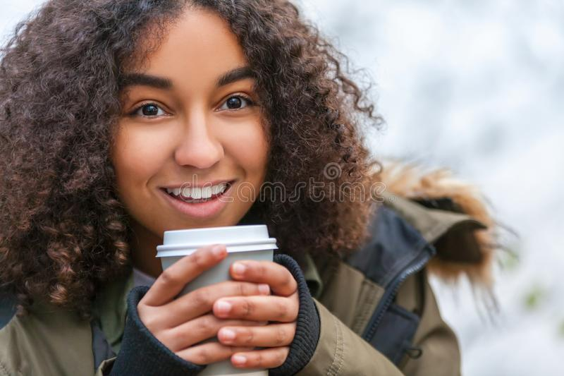 Mixed Race African American Teenager Woman Drinking Coffee. Beautiful happy mixed race African American girl teenager female young woman smiling drinking royalty free stock images