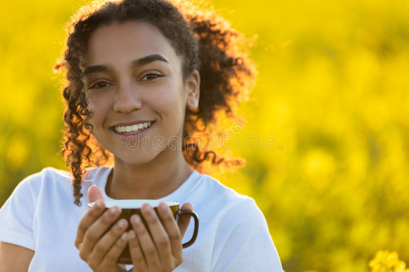 Mixed Race African American Teenager Woman Drinking Coffee Outdo. Beautiful happy mixed race African American girl teenager female young woman smiling drinking stock photo