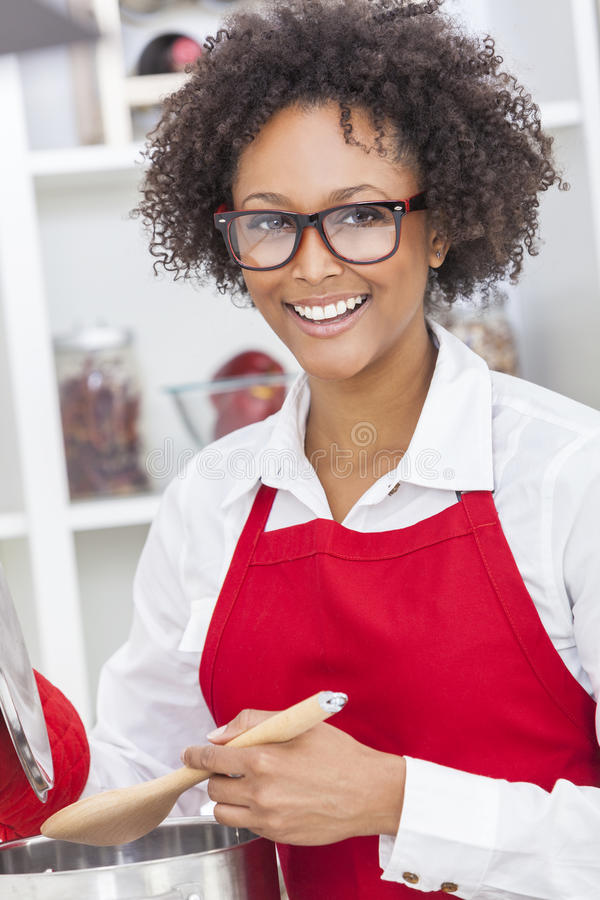 Mixed Race African American Woman Cooking Kitchen. A beautiful mixed race African American girl or young woman looking happy wearing geek glasses a red apron & royalty free stock images