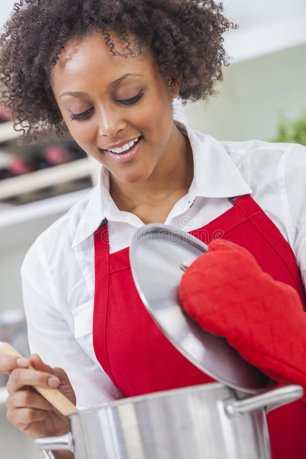 Mixed Race African American Woman Cooking Kitchen. A beautiful mixed race African American girl or young woman looking happy wearing red apron & cooking in her stock image