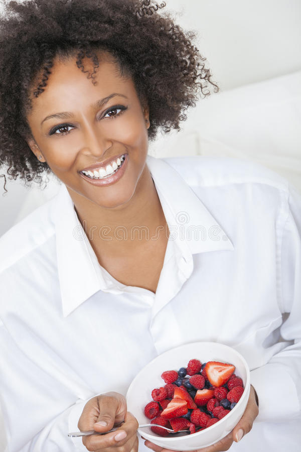 Mixed Race African American Woman Eating Fruit. A beautiful mixed race African American girl or young woman looking happy and eating fruit salad in a bowl royalty free stock photo