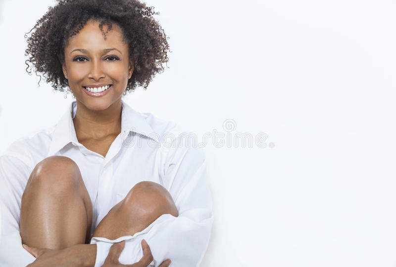 Mixed Race African American Woman Girl in White Shirt. A beautiful happy mixed race African American girl or young woman wearing a white shirt smiling with royalty free stock photo