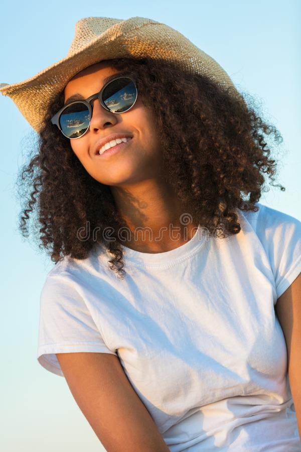Mixed Race African American Woman Sunglasses Cowboy Hat Sunset. Beautiful happy mixed race African American female girl teenager young woman wearing relective royalty free stock image