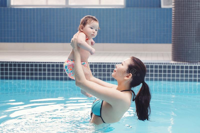 Mixed race asian mother holding her newborn baby in swimming pool stock photo